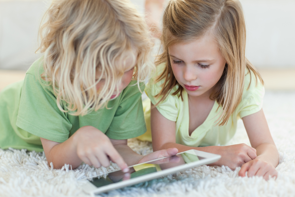 Siblings together on the floor in custom home using tablet